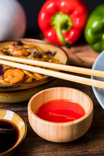 Hete spaanse pepersaus in houten kom met udonnoedels met garnalen op houten lijst Gratis Foto