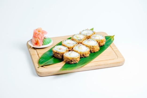 Hete sushibroodjes die op bladeren op houten raad op witte achtergrond worden gediend Gratis Foto