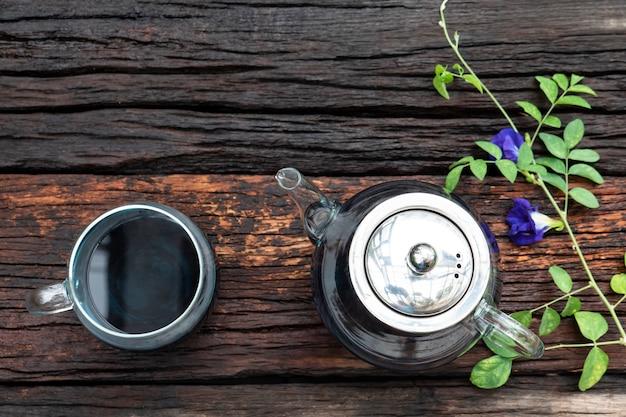 Hete thee in een glas gieten met thee van erwtenbloemen. Premium Foto