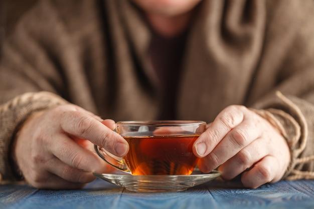 Hete thee in glazen beker in mannelijke handen Premium Foto