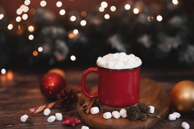 Hete winterthee in een rode mok met stervormige kerstkoekjes en warme sjaal Premium Foto