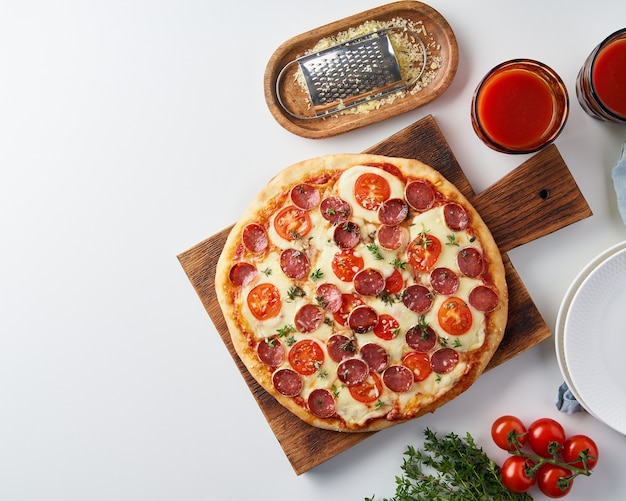 Hete zelfgemaakte italiaanse pepperoni pizza met salami, mozzarella op witte tafel, rustiek diner met worst en tomaten, bovenaanzicht, kopie ruimte Premium Foto