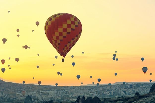 Heteluchtballonnen stijgen op bij zonsopgang, cappadocia staat wereldwijd bekend als een van de beste plekken om te vliegen met heteluchtballonnen. Premium Foto
