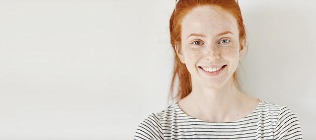 Heterochromia concept. aantrekkelijke jonge vrouw met gemberhaar en verschillende gekleurde ogen die gelukkig, geïsoleerd stellen glimlachen Gratis Foto