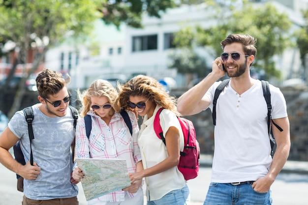 Heupmens op telefoongesprek en vrienden die kaart in openlucht controleren Premium Foto