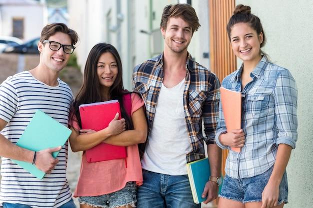 Heupvrienden die notitieboekjes houden en de camera op de straat bekijken Premium Foto