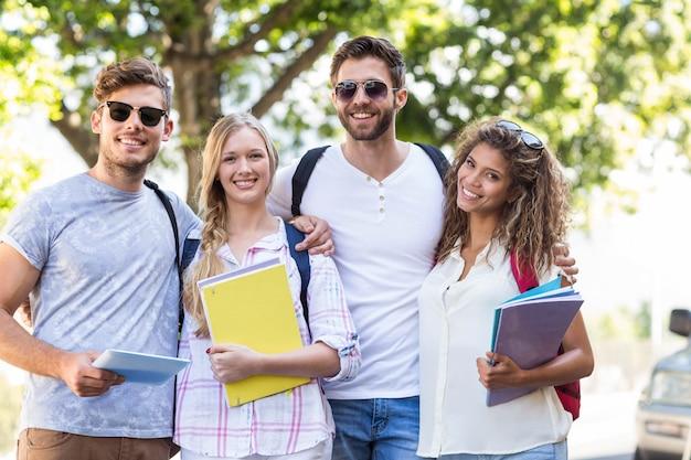 Heupvrienden die notitieboekjes houden en in openlucht bij de camera glimlachen Premium Foto