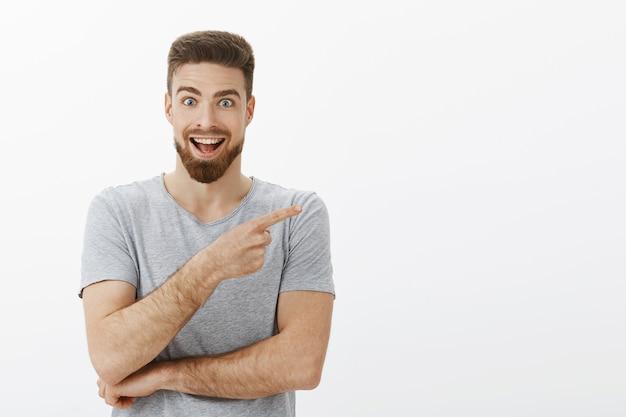 Hey deze kopie ruimte geweldig. enthousiast en opgewonden verrukt charmante mannelijke brunet met baard in grijs t-shirt wijzend naar de rechterbovenhoek gefascineerd door cool object breed glimlachend Gratis Foto