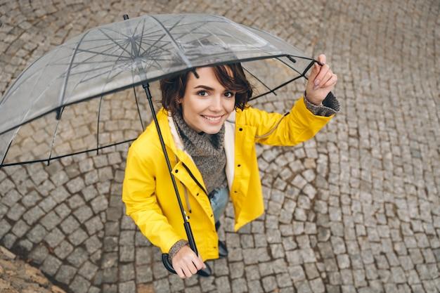 Hierboven geschoten van prachtige vrouw in gele regenjas die gelukkig zijn terwijl het lopen onder grote transparante paraplu Gratis Foto