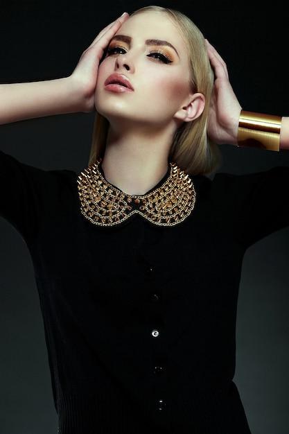 High fashion look.glamor close-up portret van mooie sexy stijlvolle blonde jonge vrouw model met fel gele make-up met perfecte schone huid met gouden sieraden in zwarte doek Gratis Foto