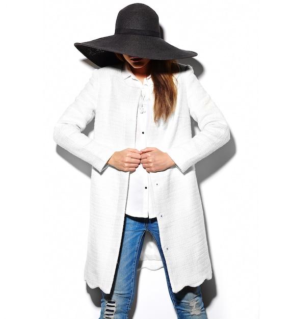 High fashion look.glamor close-up portret van mooie sexy stijlvolle brunette hipster jonge vrouw model in witte jas en grote zwarte hoed Gratis Foto