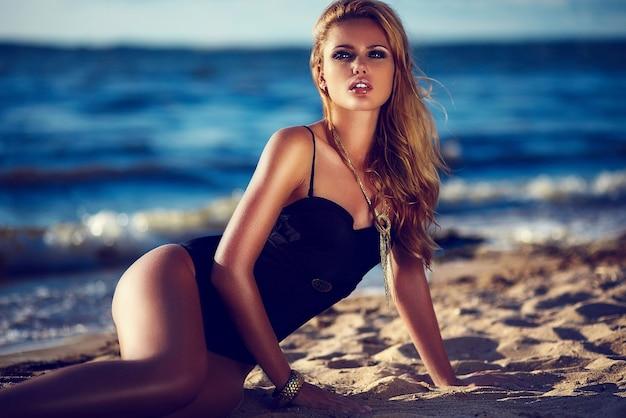 High fashion look.glamor mooie sexy stijlvolle blonde blanke jonge vrouw model met lichte make-up, met perfecte schone huid in zwart zwempak op zee strand in vogue-stijl Gratis Foto