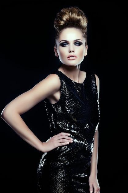 High fashion look.glamor portret van mooie sexy stijlvolle blanke jonge vrouw vrouwelijk model in zwarte jurk met lichte make-up en kapsel Gratis Foto