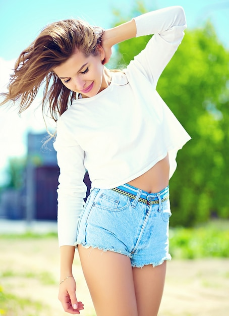 High fashion look.glamor stijlvolle sexy lachende mooie sensuele jonge vrouw model in zomer heldere hipster doek in jeans broek in de straat Gratis Foto