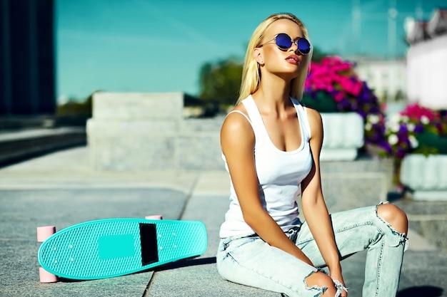High fashion look.glamor stijlvolle sexy mooie jonge blonde model meisje in zomer heldere casual hipster kleding met skateboard achter blauwe hemel in de straat Gratis Foto