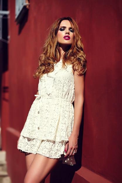 High fashion look. glamour close-up portret van mooie sexy stijlvolle blonde jonge vrouw model met lichte make-up en roze lippen met perfecte schone huid in witte zomerjurk in de buurt van rode stadsmuur Gratis Foto