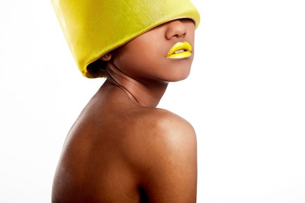 High fashion look.glamour fashion mooie zwarte amerikaanse vrouw met gele heldere lippen met geel materiaal op hoofd op wit wordt geïsoleerd Gratis Foto