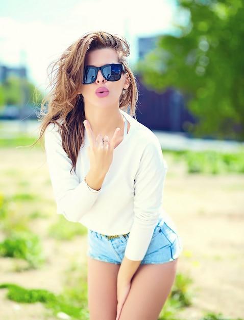 High fashion look. glamour stijlvolle sexy lachende mooie sensuele jonge vrouw model in zomer heldere hipster doek in jeans shorts in de straat geven rock and roll teken Gratis Foto