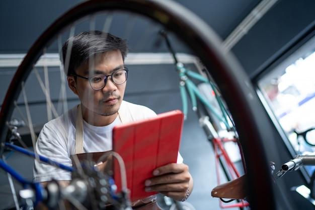 Hij gebruikt een tablet om het product te controleren. de ingang van de fietsenwinkel zorgt voor de fietsen van de klanten voor het controleren van de staat. Premium Foto