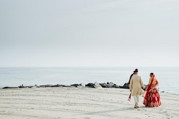 Hindoe bruidspaar loopt langs de oceaan kust Gratis Foto