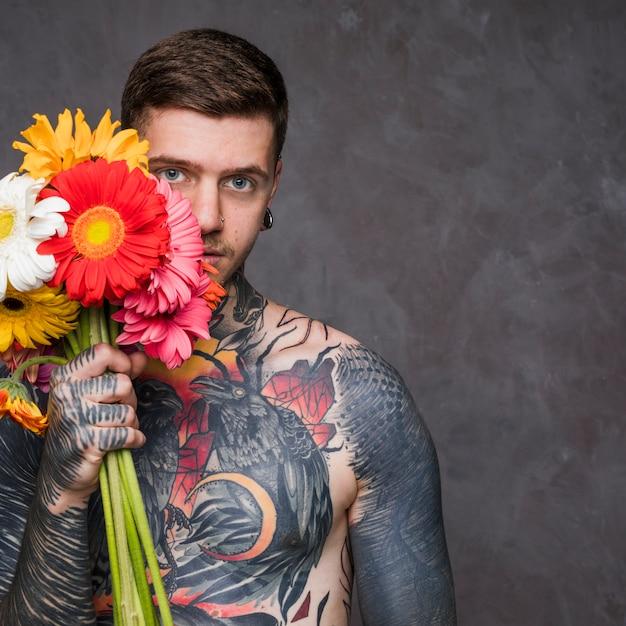 Hipster getatoeëerde jonge man met kleurrijke gerbera bloemen in de hand staande tegen een grijze achtergrond Gratis Foto