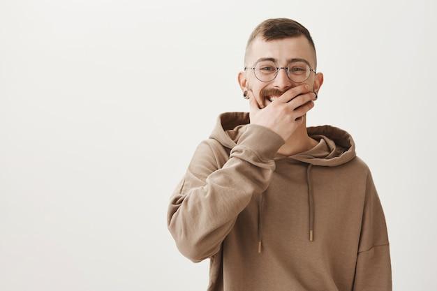 Hipster in hoodie en glazen lachen, bedek de mond met de hand terwijl je grinnikt Gratis Foto