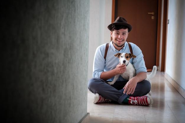 Hipster jonge man poseren met jack russell hond Premium Foto