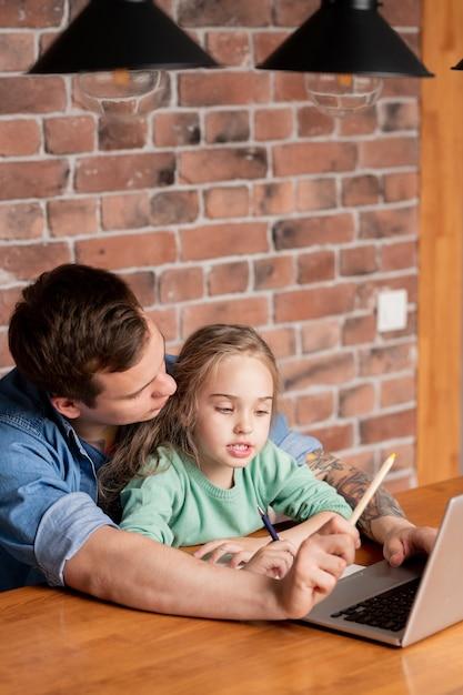 Hipster jonge vader met tatoeage op arm aan tafel zitten met dochter en het gebruik van laptop terwijl ze haar helpt voor te bereiden op schooltest Premium Foto