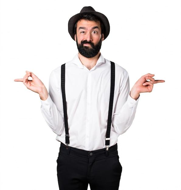 Hipster man met baard die naar de laterals wijst en twijfels heeft Gratis Foto