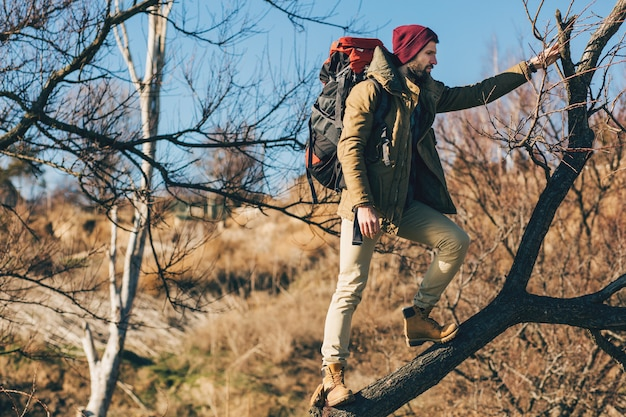 Hipster man reizen met rugzak in herfst bos dragen warme jas, hoed, actieve toerist, natuur in koude seizoen verkennen Gratis Foto