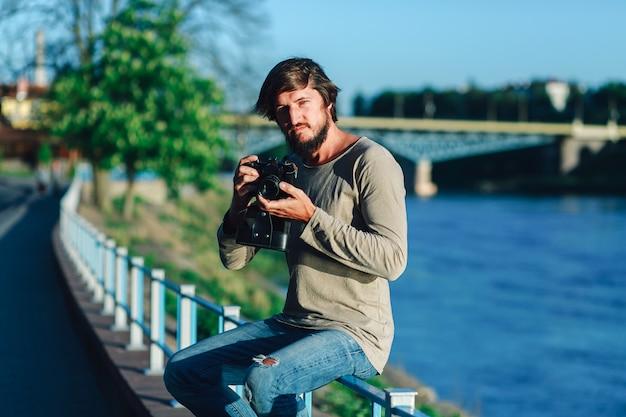 Hipster man schoot fotografie van hem filmcamera op straat publiek Premium Foto