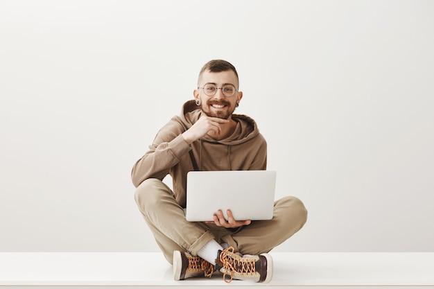 Hipster man zit met gekruiste benen met laptop en glimlachend tevreden Gratis Foto