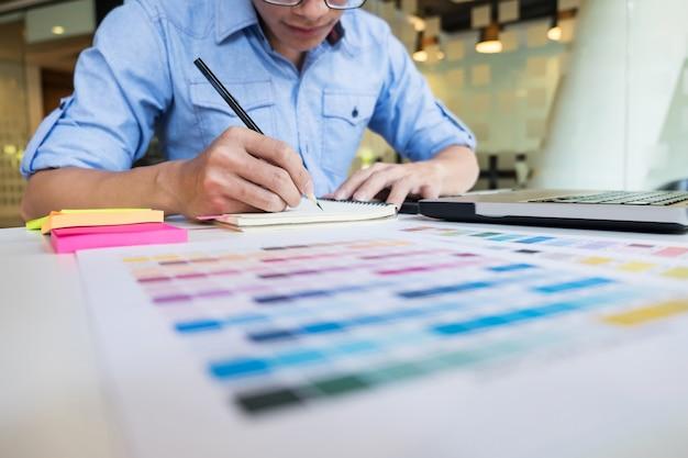 Hipster moderne grafische ontwerper tekening werken thuis met behulp van laptop op kantoor. Gratis Foto