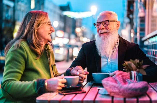Hipster schakelde senior paar verliefd koffie drinken in openlucht café bar Premium Foto
