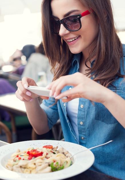 Hipster vrouw die een foto van italiaanse maaltijd neemt Gratis Foto