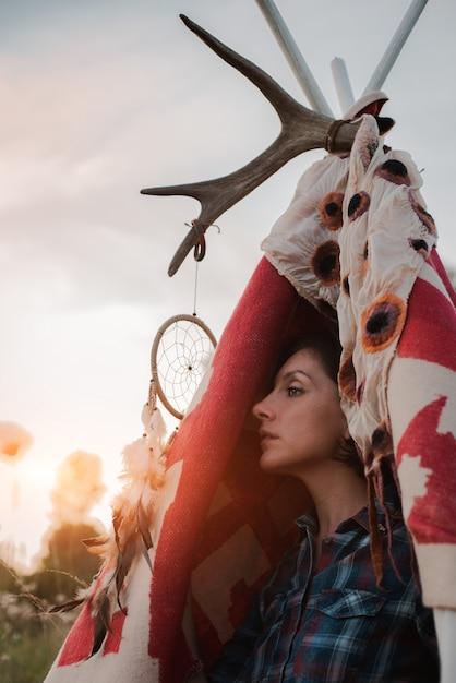 Hipstervrouw in de vorm van een sjamaan zoekt inspiratie van moeder aarde in een wigwam in de natuur. Premium Foto