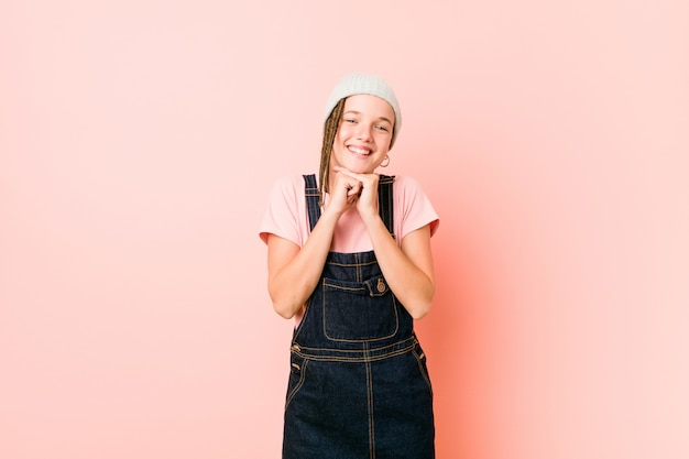 Hispter tienervrouw houdt handen onder kin, kijkt gelukkig opzij. Premium Foto