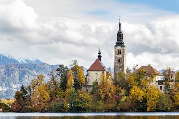 Historisch kasteel omringd door groene bomen in de buurt van het meer onder de witte wolken in bled, slovenië Gratis Foto