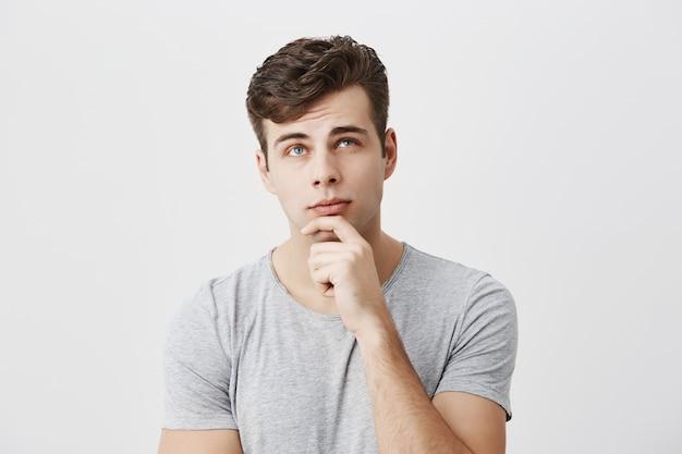 Hmm niet slecht. geconcentreerde, doordachte mannelijke student die zijn kansen om te slagen voor het examen evalueert, de kin op de hand houdt, probeert te beslissen wat hij verdient. mensen, levensstijl, gezichtsuitdrukkingen. Gratis Foto