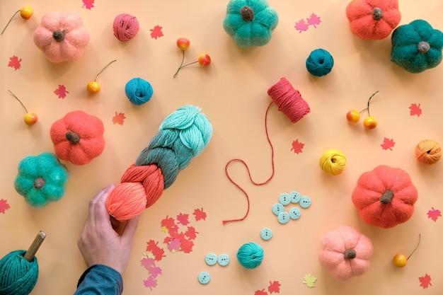 Hobby-ambacht plat gelegd. herfst seizoensgebonden achtergrond met diy vilten wol pompoenen, wol bundel, knopen en bes. Premium Foto