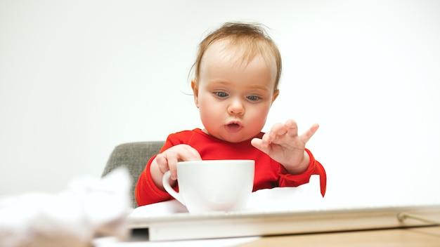 Hoe moe ik ben. kind babymeisje zit met toetsenbord van moderne computer of laptop in het wit Gratis Foto
