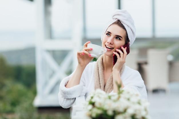 Hoe zit het met koffie in de frisse lucht, telefonisch spreken. ontspannen op het terras van een luxe villa met een kopje koffie of thee. Premium Foto