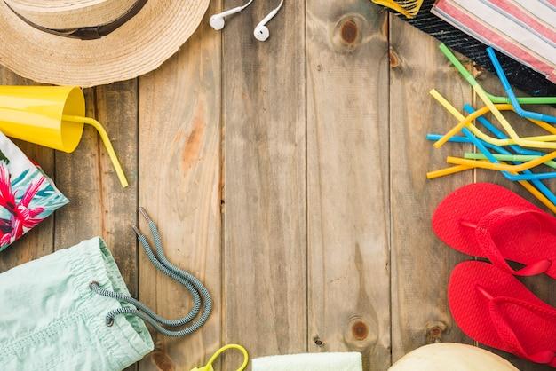 Hoed in de buurt van oortelefoons en flip-flops met beker en rietjes Gratis Foto