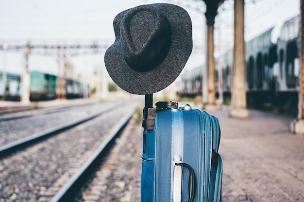 Hoed zat op een koffer op een treinstation. Premium Foto