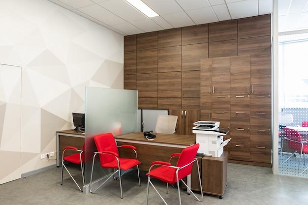 Hoek van modern kantoor met witte en houten muren, grijze vloer, open plek met rode en witte fauteuils en kamers achter de glazen wand Premium Foto