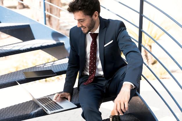 Hoge hoek advocaat in pak die op laptop werkt Gratis Foto