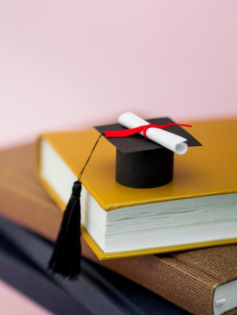 Hoge hoek afstuderen cap en diploma op verschillende boeken Gratis Foto