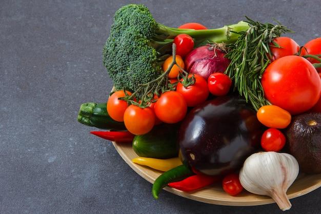 Hoge hoek bekijken een tros tomaten met chili pepers, ui, aubergine, groenen, broccoli, knoflook op grijze ondergrond. horizontaal Gratis Foto