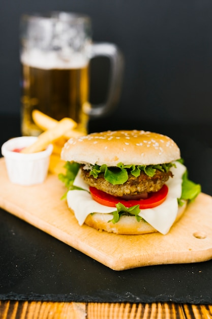 Hoge hoek close-up hamburger met frietjes op plaat Gratis Foto