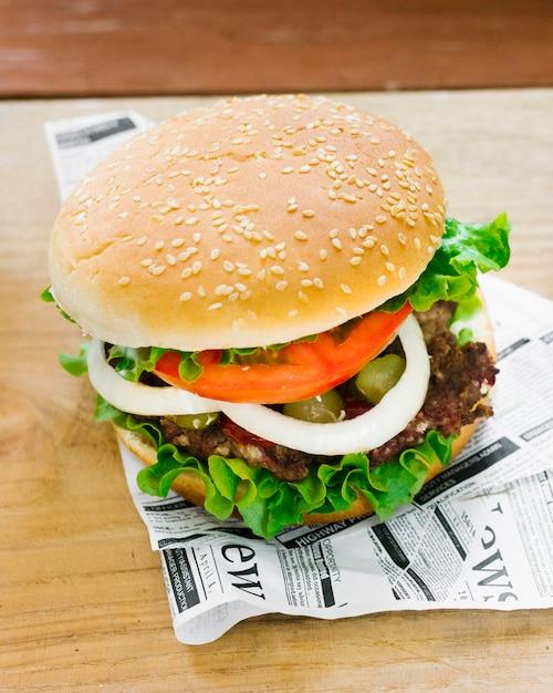 Hoge hoek close-up hamburger op krant Gratis Foto